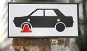 foto of illegal  - Traffic sign icon of an illegally parked car on wheel clamp - JPG