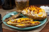 image of baked potato  - A twice baked potato potato skins and baked potato peals with a beer and sour cream in the background - JPG