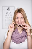 foto of snellen chart  - Young attractive woman trying on new glasses - JPG