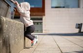 Постер, плакат: Little girl with sneakers and hoodie training outdoors