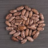 foto of pinto bean  - Top view of circle of pinto beans against grey vinyl background - JPG