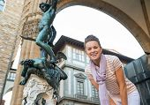 foto of perseus  - Portrait of happy young woman in front of statue perseus with the head of medusa in florence italy - JPG