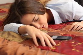 picture of fatigue  - Close up portrait of a business woman tired and sleeping in an hotel bed with a mobile phone - JPG