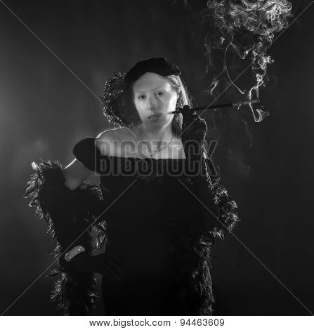 Black and white portrait of glamorous woman smoking cigarette and dressed in vintage clothing standing with hand on hip waist up portrait in 1940s film