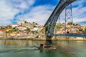 stock photo of old boat  - Porto and old traditional boats with wine barrels in Portugal in a summer day - JPG