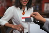 stock photo of cashiers  - Cashier using small credit card reader to accept payment - JPG