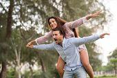stock photo of piggyback ride  - Man giving his girlfriend piggyback ride in the park - JPG
