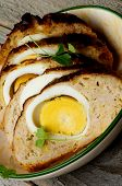 picture of meatloaf  - Slices of Delicious Homemade Meatloaf Stuffed with Boiled Eggs in Bowl closeup on Rustic Wooden background - JPG