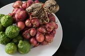 foto of red shallot  - Raw bergamot and shallot in a plate on black background - JPG
