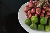image of red shallot  - Raw bergamot and shallot in a plate on black background - JPG