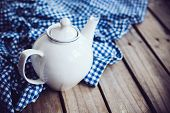 foto of teapot  - Large white porcelain teapot and a blue linen napkin on old wooden board, rustic kitchen background. ** Note: Soft Focus at 100%, best at smaller sizes - JPG