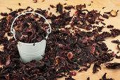 foto of bucket  - White bucket with dried hibiscus on the wooden floor as a background - JPG