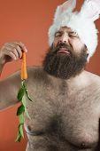 stock photo of blubber  - Crying bearded fat man wears silly bunny ears - JPG