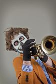 picture of clown face  - Professional trumpet player with face painted as human skull - JPG
