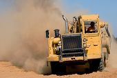 stock photo of heavy equipment  - earth mover in action creating dirt and dust - JPG