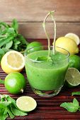 foto of mint-green  - Glass of green healthy juice with mint and fruits on wooden background - JPG
