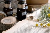 picture of roughage  - Old book with dry flowers and bottles on table close up - JPG