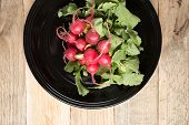 foto of radish  - Red radishes in black bowl on weathered wood background - JPG