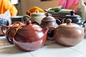 stock photo of loam  - Many old style Chinese Teapots on white table