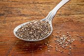picture of tablespoon  - tablespoon of chia seeds against rustic - JPG