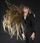 image of hair blowing  - Smiling Blond Woman Wearing Black Dress Standing in Studio with Black Background with Long Hair Blowing in Strong Wind - JPG