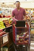 picture of trolley  - Man Pushing Trolley By Fruit Counter In Supermarket - JPG