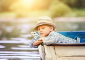 foto of life-boat  - Dreaming boy lying in old boat on the river - JPG