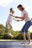 foto of bouncing  - Mother And Daughter Bouncing On Trampoline Together - JPG