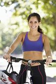 image of riding-crop  - Woman Cycling Through Park - JPG