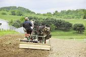 image of hilltop  - The back of an Amish man cultivating his hilltop field in the springtime with a cultivator and a pair of horses - JPG