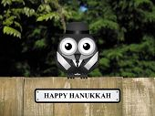 image of bird fence  - Comical bird with happy Hanukkah message perched on a timber garden fence against a foliage background - JPG