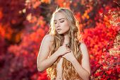 foto of chest hair  - young woman on a background of red and yellow autumn leaves with beautiful curly hair on his chest - JPG