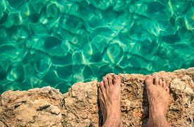 foto of barefoot  - Naked human barefoot on rock cliff ready to jump in the clear blue water  - JPG