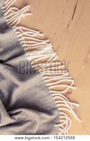warm wool throw plaid on wooden background