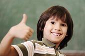 Постер, плакат: Счастливый мальчик в классе с пальца вверх: Зеленый плата за