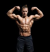 Athletic Man Posing. Photo Of Man With Perfect Physique On Black Background. Strength And Motivation poster