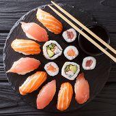Japanese Sushi On A Rustic Dark Background. Sushi Rolls, Nigiri, Maki, Soy Sauce. Sushi Set On A Tab poster