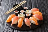 Japanese Sushi On A Rustic Dark Background. Sushi Rolls, Nigiri, Maki, Soy Sauce. Sushi Set On A Tab poster