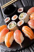Постер, плакат: Set Of Sushi With Salmon And Tuna California Rolls Maki Soy Sauce Closeup On A Black Slate Board