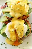 stock photo of benediction  - Delicious eggs benedict with hollandaise sauce with avocado with egg yolk - JPG