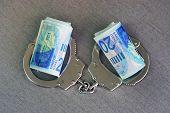Roll Israeli Money Bills (banknotes) Of 200 Shekel In Handcuffs. Shekel Bills With Handcuffs. Handcu poster