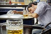 image of bing  - Young man passed out drunk with beer bocks on the glass table of an outdoor terrace - JPG