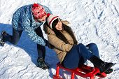 stock photo of toboggan  - Portrait of happy couple tobogganing in winter - JPG