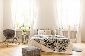 Comfy Bedroom Interior With A Leaf Motif Bedding On A Bed, A Rattan Chair And A Black And White Pouf poster