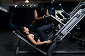 Fit Woman Working Out With Trainer At The Gym, Woman Doing Muscle Training At The Gym. Athlete Worki poster
