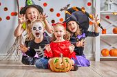 Happy brother and three sisters on Halloween. Funny kids in carnival costumes indoors. Cheerful chil poster