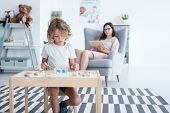 Boy Sitting At The Table And Playing With Blocks While His Counselor Is Taking Notes poster