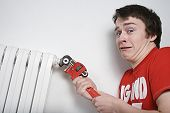 stock photo of minion  - Plumber boy with stillson wrench about to put loads of water flooding on the floor - JPG