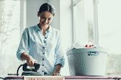 Young Smiling Woman Ironing Clothes After Laundry. Happy Beautiful Girl Enjoying Ironing Clean And F poster