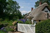 stock photo of english cottage garden  - english cottage thatch roof white gate garden - JPG